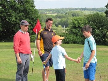 Fathers and sons shaking hands on Elstree School Golf course